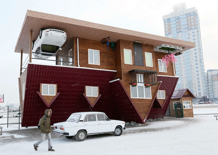 A man passes a house built upside-down in Russia's Siberian city of Krasnoyarsk