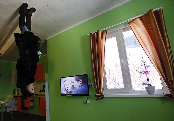 A woman visits a room in a house built upside-down in Russia's Siberian city of Krasnoyarsk