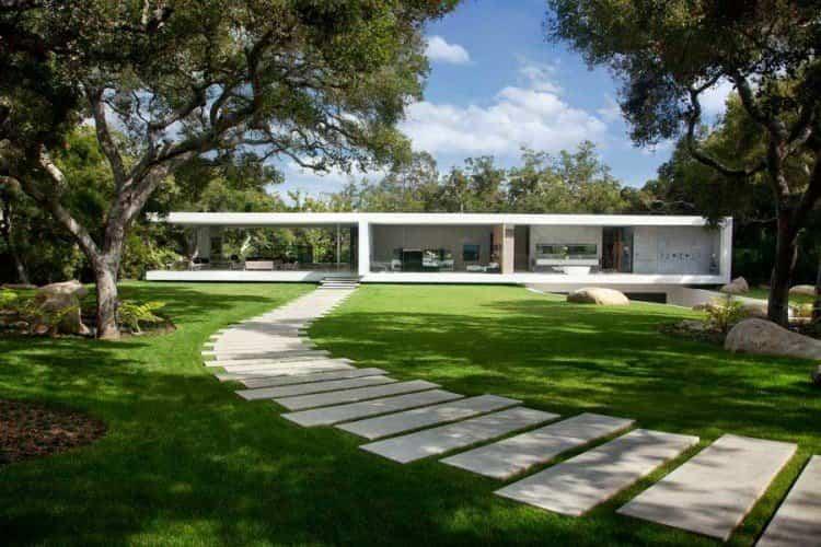 casa transparente rodeada de un gran jardín