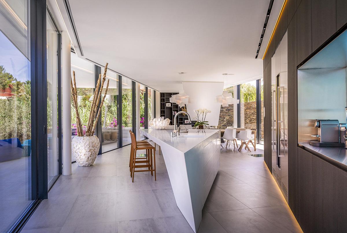 Casa moderna a orillas del Mediterráneo con cocina con una isla en mitad