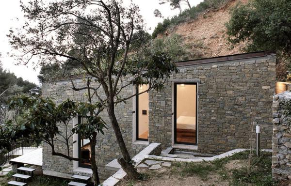 pequeña casa construida en la ladera de la montaña con un diseño de piedra natural