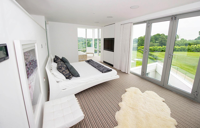 mansión subterránea inglaterra - dormitorio con vistas al jardín